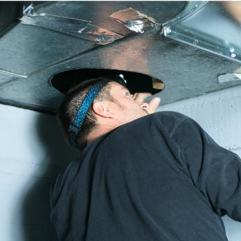 Technician checking a duct